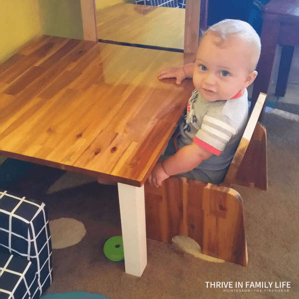 7 month old baby sitting at a DIY weaning table wooden with white legs.