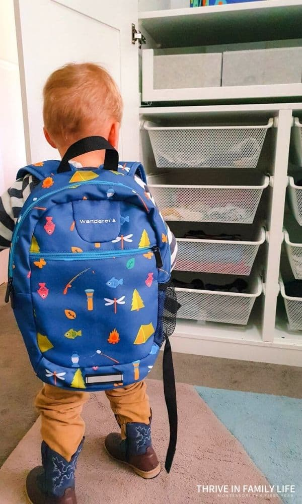 IKEA Pax kids closet with 4 white mesh baskets on bottom with toddler boy holding door open while wearing kids backpack.