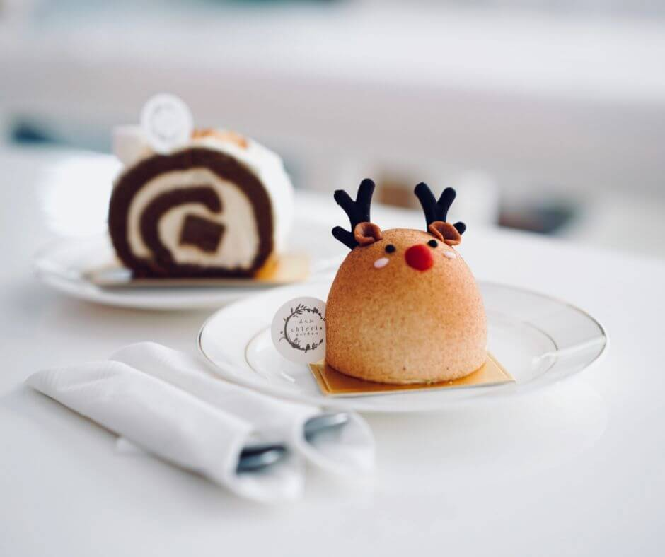 Christmas dinner on a a budget to cut costs with a reindeer dessert and chocolate scroll behind it on a white table.