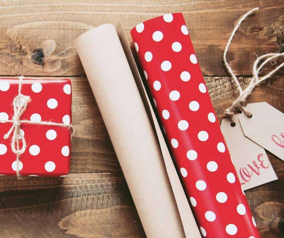 Free christmas wrapping paper and gift tags that are red and polka dots on wooden table
