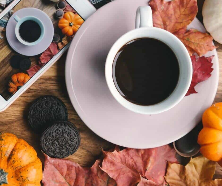 cup of coffee with small pumpkins and Oreos on a wooden table covered with autumn leaves at Halloween dinner.