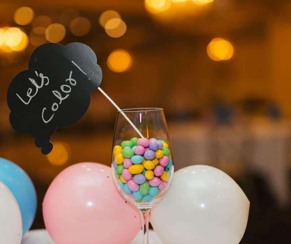 Halloween coloring table with a chalkboard sign in wine glass full of candy sitting on a table covered in balloons.