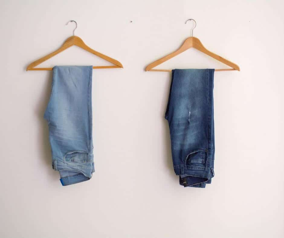 home capsule wardrobe with two pairs of jeans on separate wooden hangers on white wall.