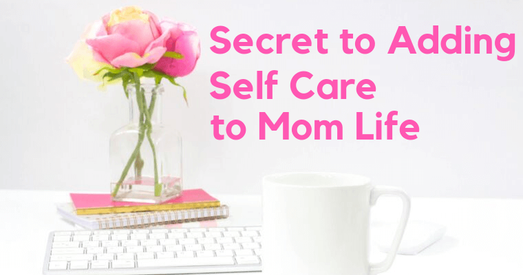 pink roses in clear vase on a pink book about self care for moms