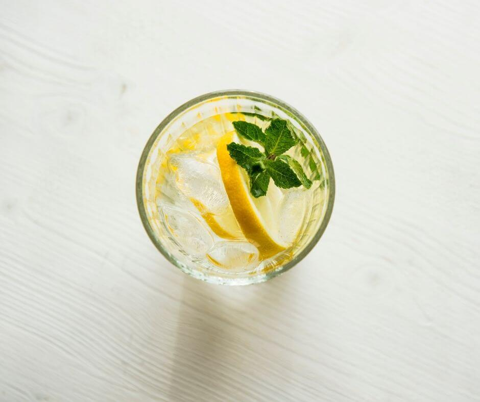 glass of water with lemon and mint on a white table to prevent snacking.