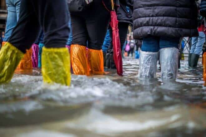 Group of people standing in a flood with rainbow boot covers to prepare for natural disaster