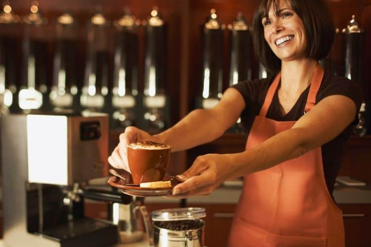 random acts of kindness challenge for moms with barista handing a coffee out