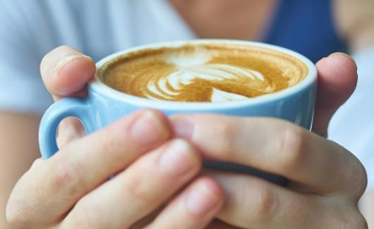 drink a warm coffee when you get up to start a positive day as sahm with latte in blue mug in womens hands