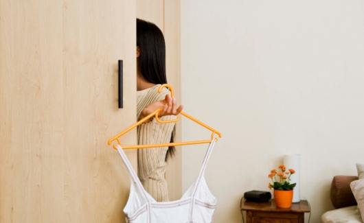 Get dressed to start a positive day as sahm mom with black haried women reaching into closet while holding yellow hanger with white tank top