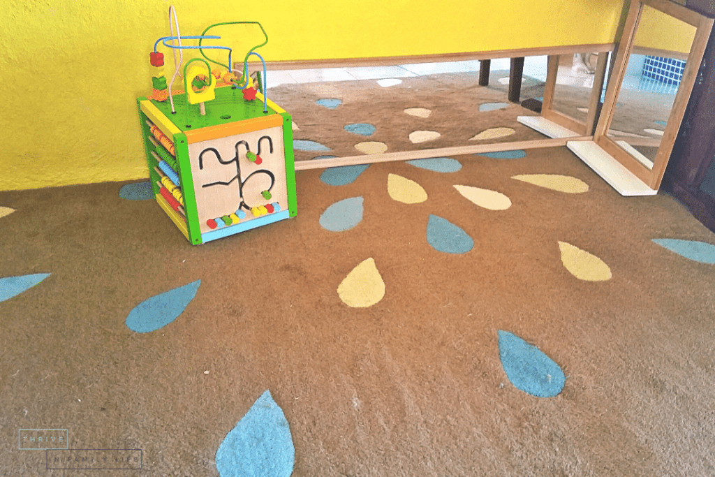 Montessori Play Area for 6 month old baby with rug, mirrors, and box.