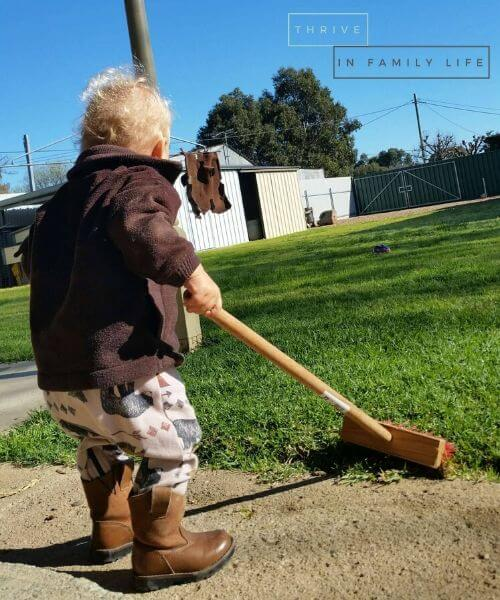 1 year old boy sweeping outside for outdoor montessori play