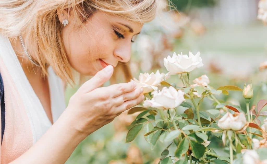 woman smelling flowers as gratitude photo challenge