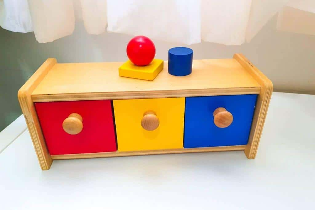 Montessori toy for 12 month old that is red, yellow, and blue sorting box.