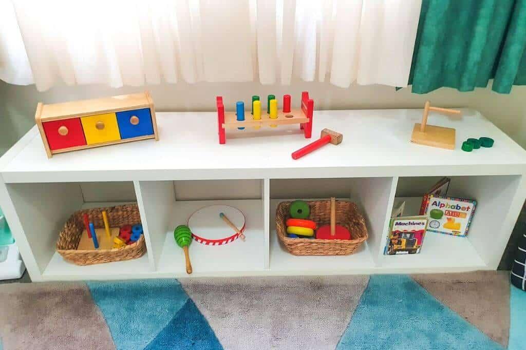 Montessori shelf for 12 month old with Montessori toys on it.