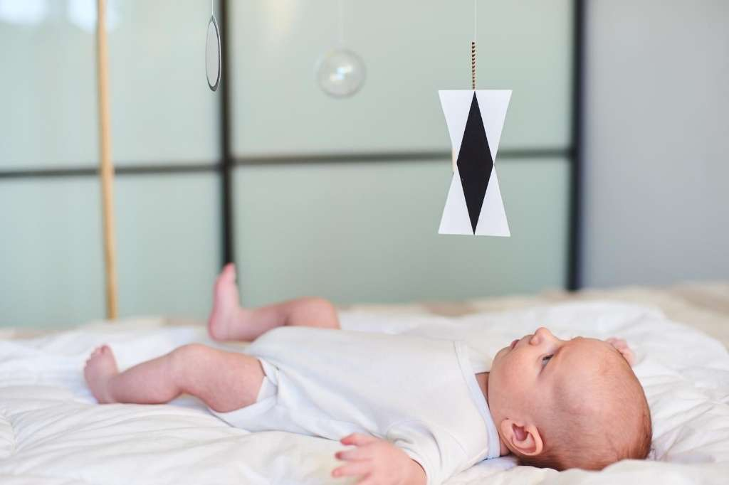 Montessori Munari mobile and newborn on white blanket.