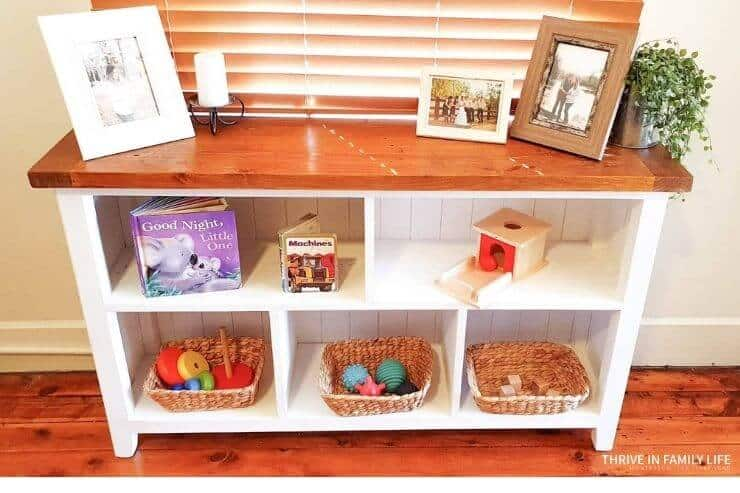 Montessori shelf for 7 month old with wooden top and white bookshelves with toys for 7 month old including books, object box, blocks, and stacker.