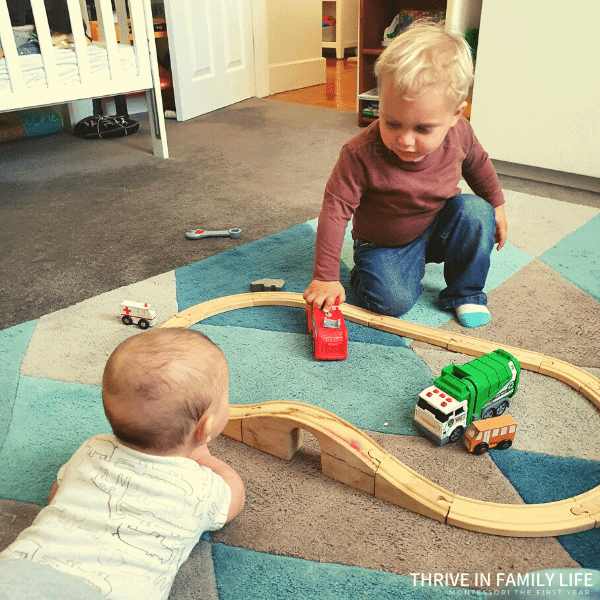 two brothers baby and toddler playing with wooden train set montessori at home multiple children