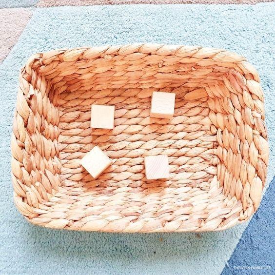 4 wooden cube blocks in a woven basket
