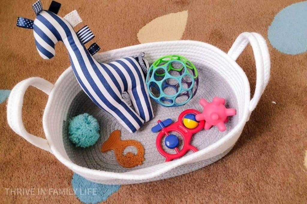Montessori baby exploration basket for 5 month old with sensory ball, rattle, teething fish, and soft giraffe toy.