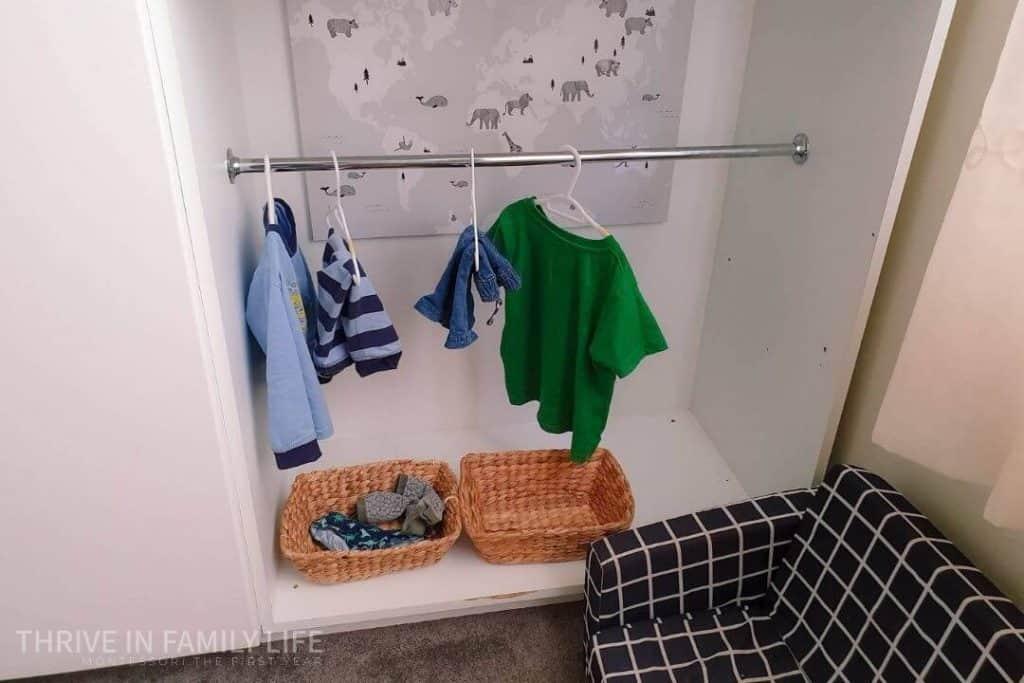 Montessori toddler closet with pajama set, shirt, pants, and basket of socks and undies.