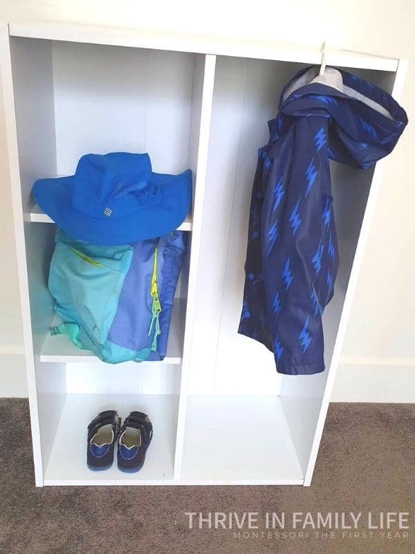 Montessori Entryway Australia example with DIY Montessori Entryway set-up for Montessori toddler coat rack.  Blue jack, hat, backpack, and shoes stored in this white open shelf.