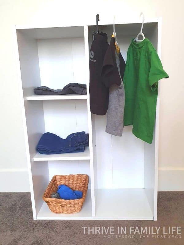 Montessori Wardrobe Australia example with white Bunnings shelf and clothes hanging with pants folded on shelf within.