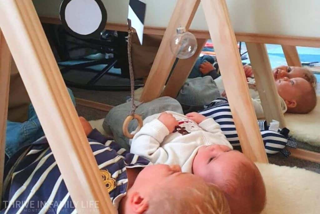 3 month old with DIY munari mobile and toddler brother