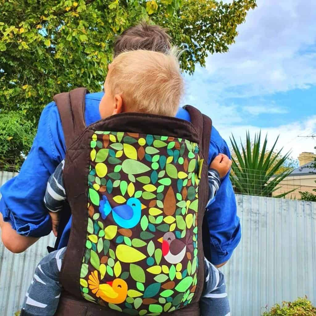 1 year old in Tweet Boba carrier with brown straps and colorful birds and leaves. On dads back.