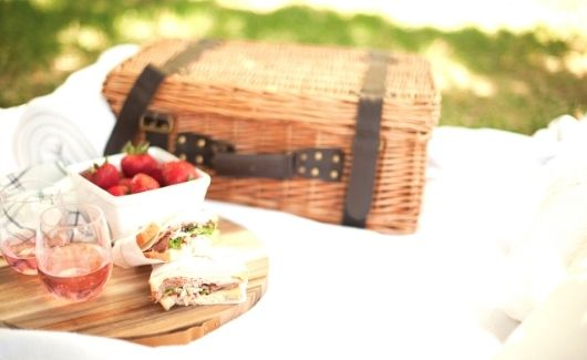 valentines day picnic in backyard with wicker basket, 2 roast beef sandwiches, 2 classes of rose, and bowl of strawberries on wooden chopping board all on white blanket in grass.