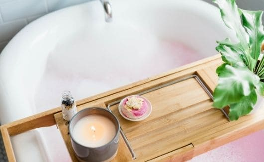 valentines spa date night at home with bathtub with candle, sweet pink dessert, plant, and essnetial oil on bath board/table.