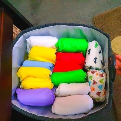 grey cloth diaper storage basket with pocket cloth diapers of variety of colors.