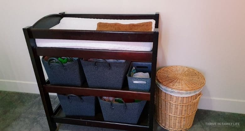 brown,wooden montessori change table with 2 shelves with 2 grey baskets on each filled with nappies. wicker basket with wet bag in it next to it.