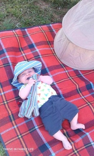 Montessori 3 month old on a red picnic blanket outdoor play with blue hat and giraffe stuffed toy being chewed on