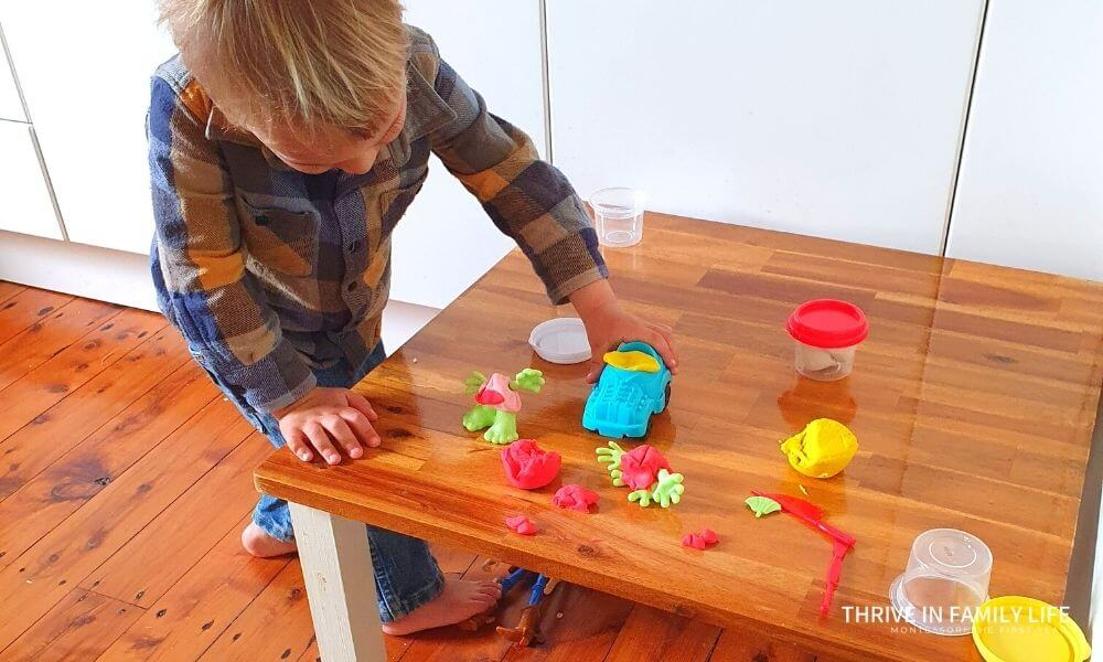 Montessori Weaning table for activities being used with 2 yr old with play doh.