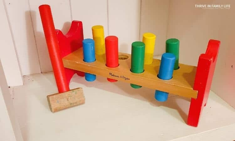 Melissa & Doug wooden hammer and peg toy on Montessori  white shelf