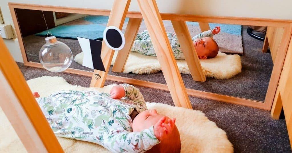 Montessori newborn baby in zipper jumpsuit under DIY munari mobile next to floor mirror while laying on sheepskin rug