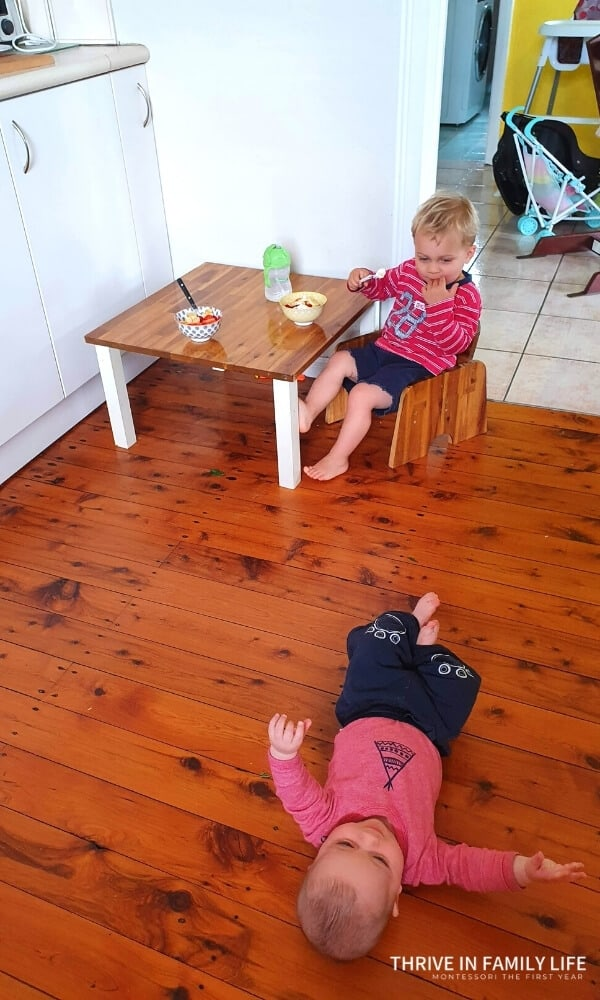 Montessori weaning table being used by 2 year old while 3 month old brother on the floor in kitchen. Bowls of yogurt on the table with green drink bottle.