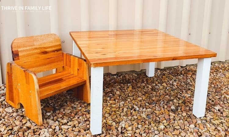 DIY montessori weaning table and chair on rocks in front of tan shed wall