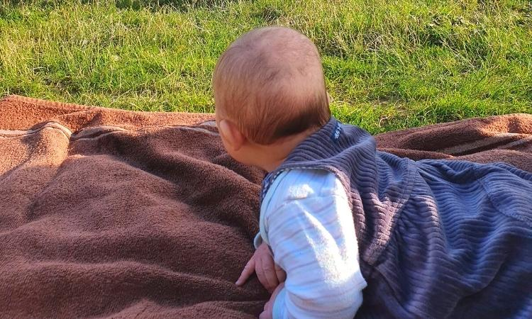 2 month old baby on a brown towel on grass for outside Montessori baby play.