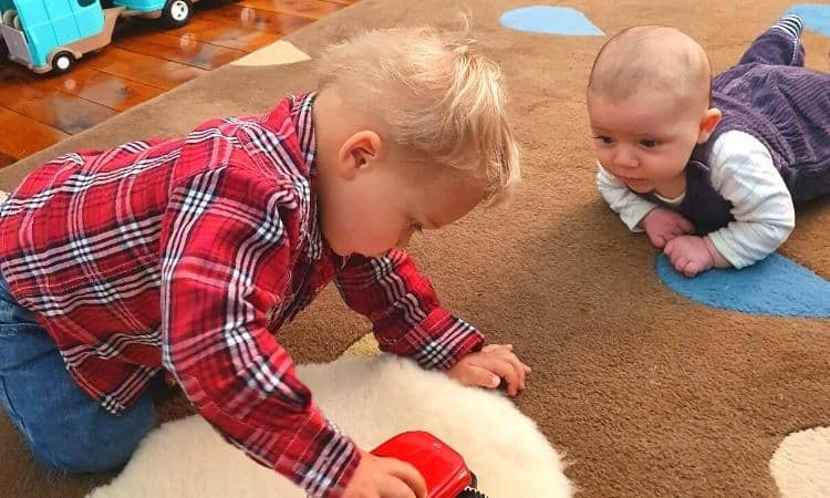 Montessori siblings on rug with 2 month old baby doing tummy time while watching 2 yr old brother in red shirt and jeans play with red truck on floor.