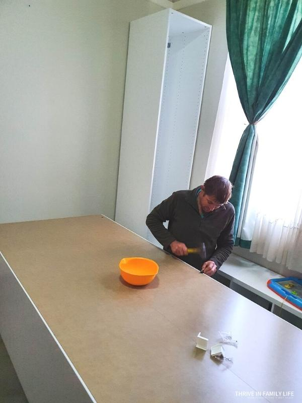 Man in green jumper with hammer building IKEA Pax wardrobe while on floor