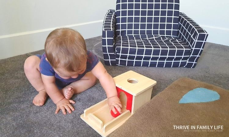 object permanence box wooden with red ball being played with by montessori 8 month old baby on grey carpet next to dark blue kids couch