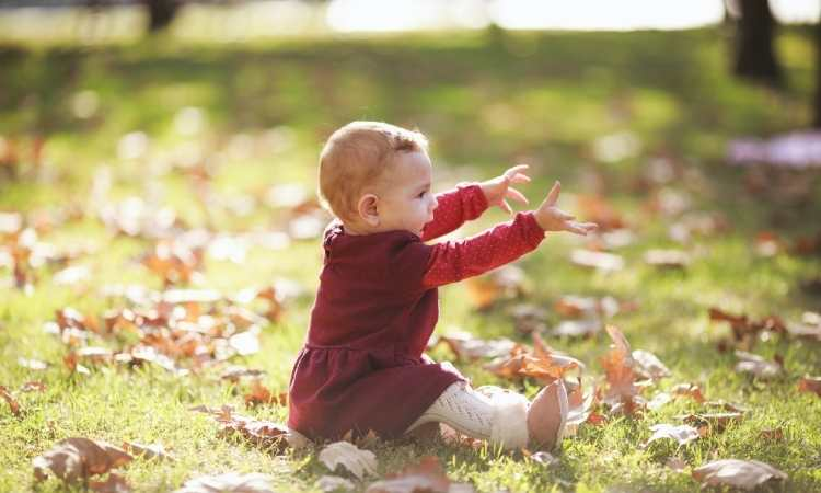 baby in red dress and white tights sitting on grass and brown leaves with arms out smiling