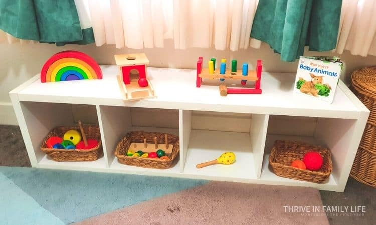 Montessori shelf 8 month old white with 8 toys on it including wooden rainbow, object permanence box, hammer and pegs toy, animal board book, stacking rings wooden, yellow maraca, 2 texture balls orange and red. All at child height.